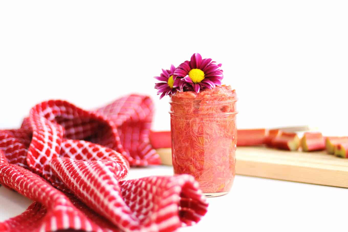A jar of rhubarb jam with purple flowers and a red towel