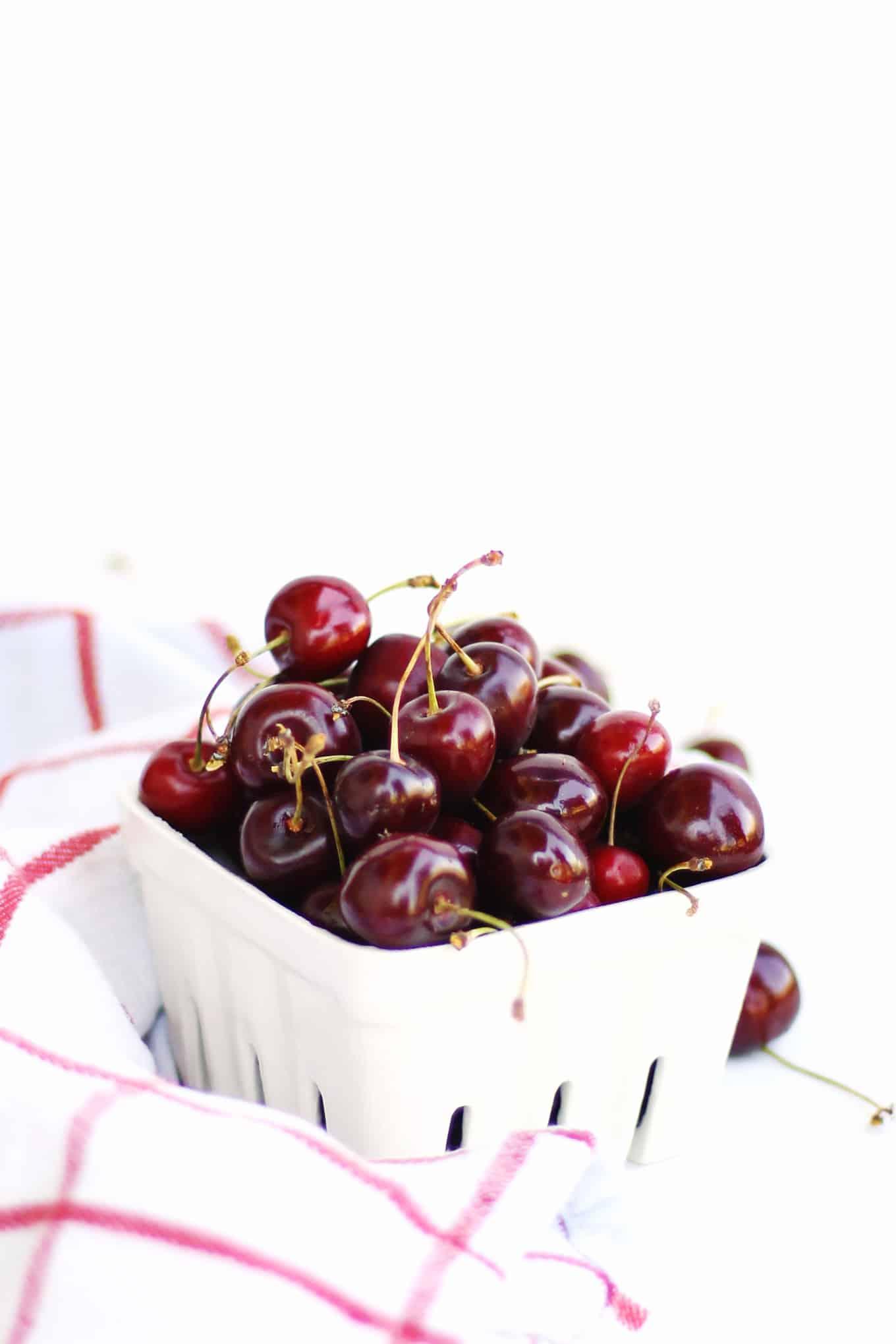 Cherries in a white farmers market basket