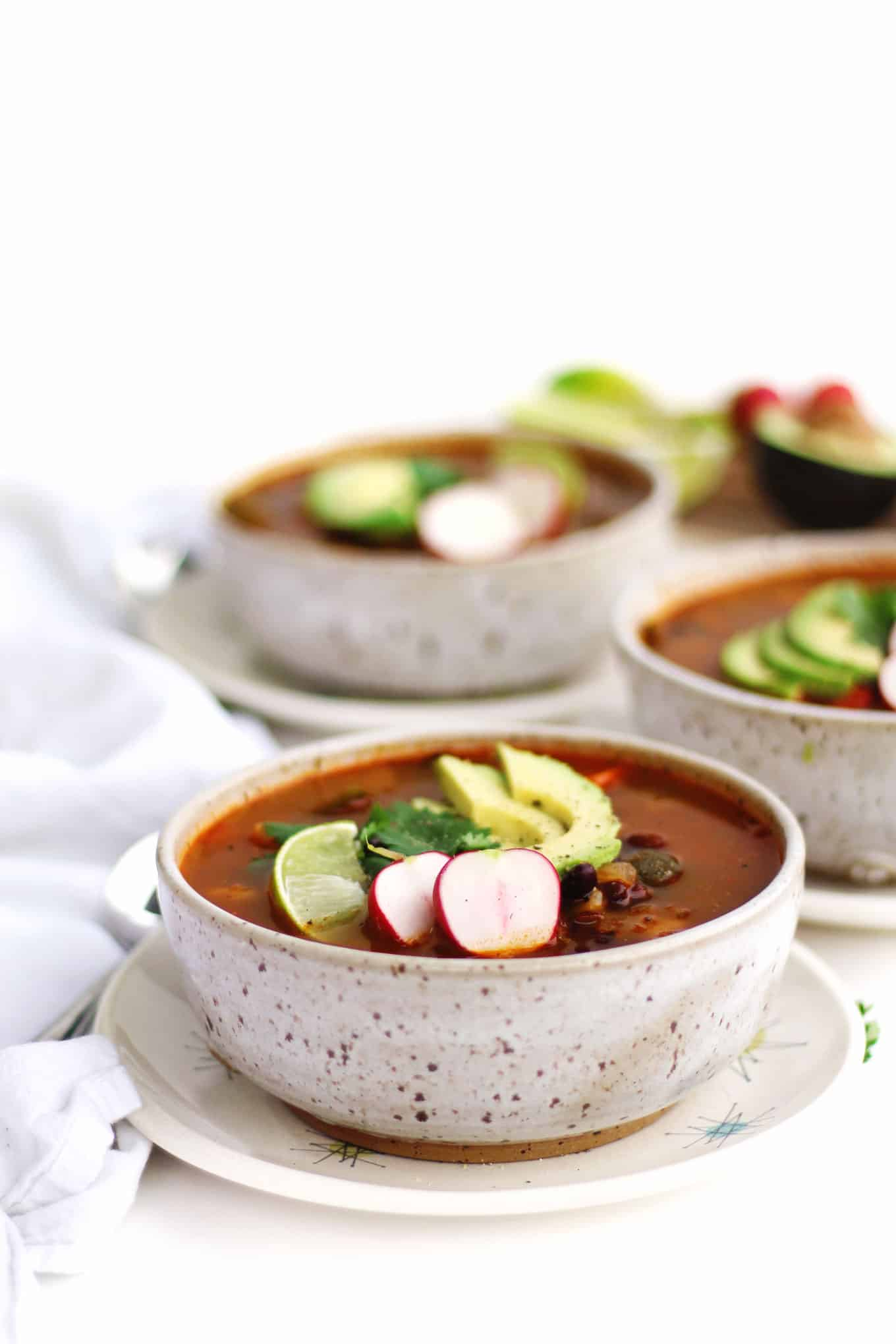 bowl of hominy soup with radishes and avocado