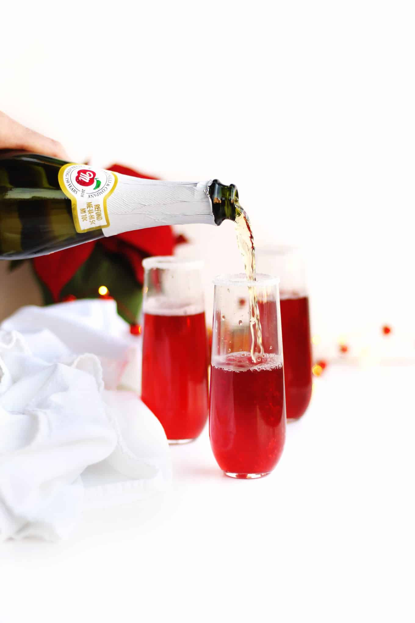 pouring apple cider into a cranberry mimosa mocktail