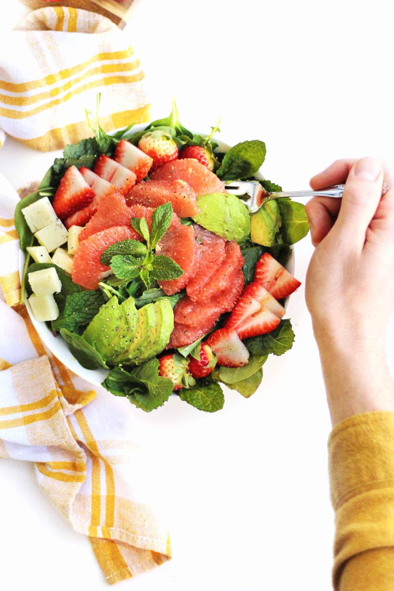 grapefruit avocado salad with hand and fork
