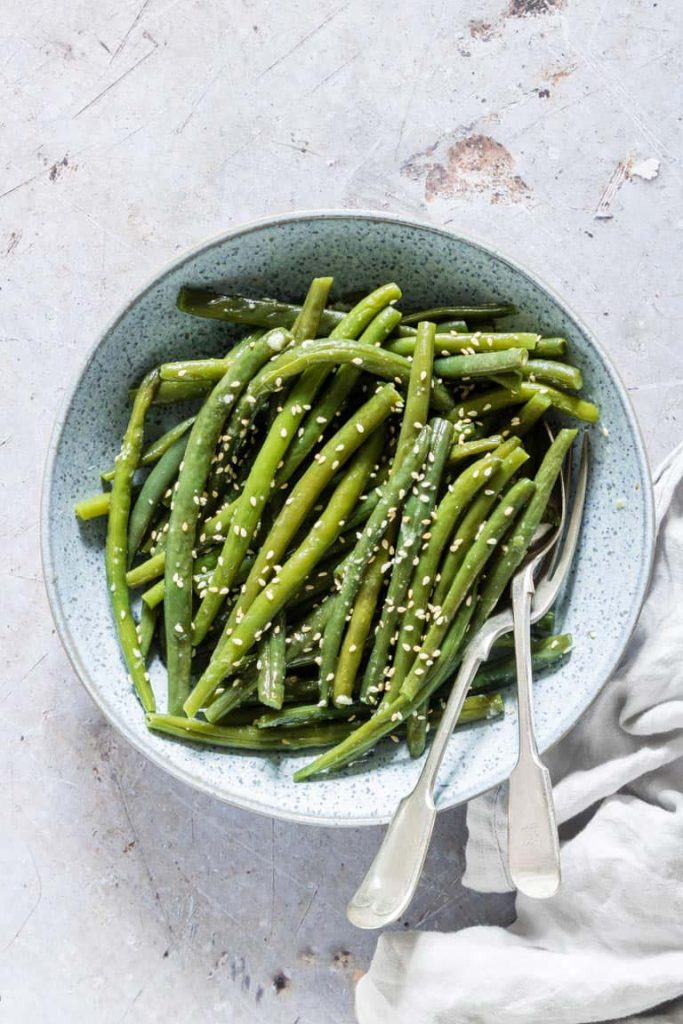 sesame green beans in a bowl with two forks
