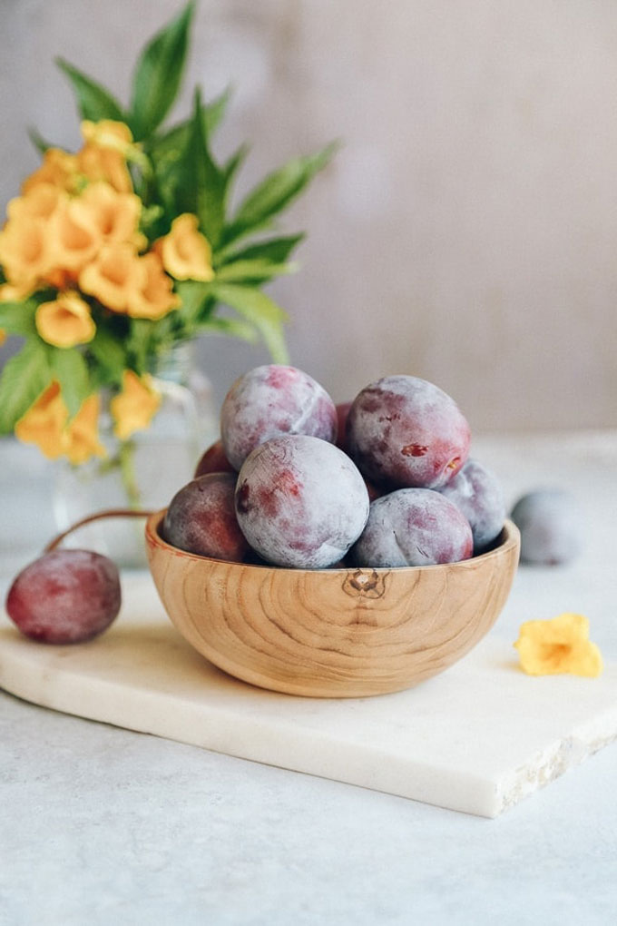 fresh plums in a wooden bowl
