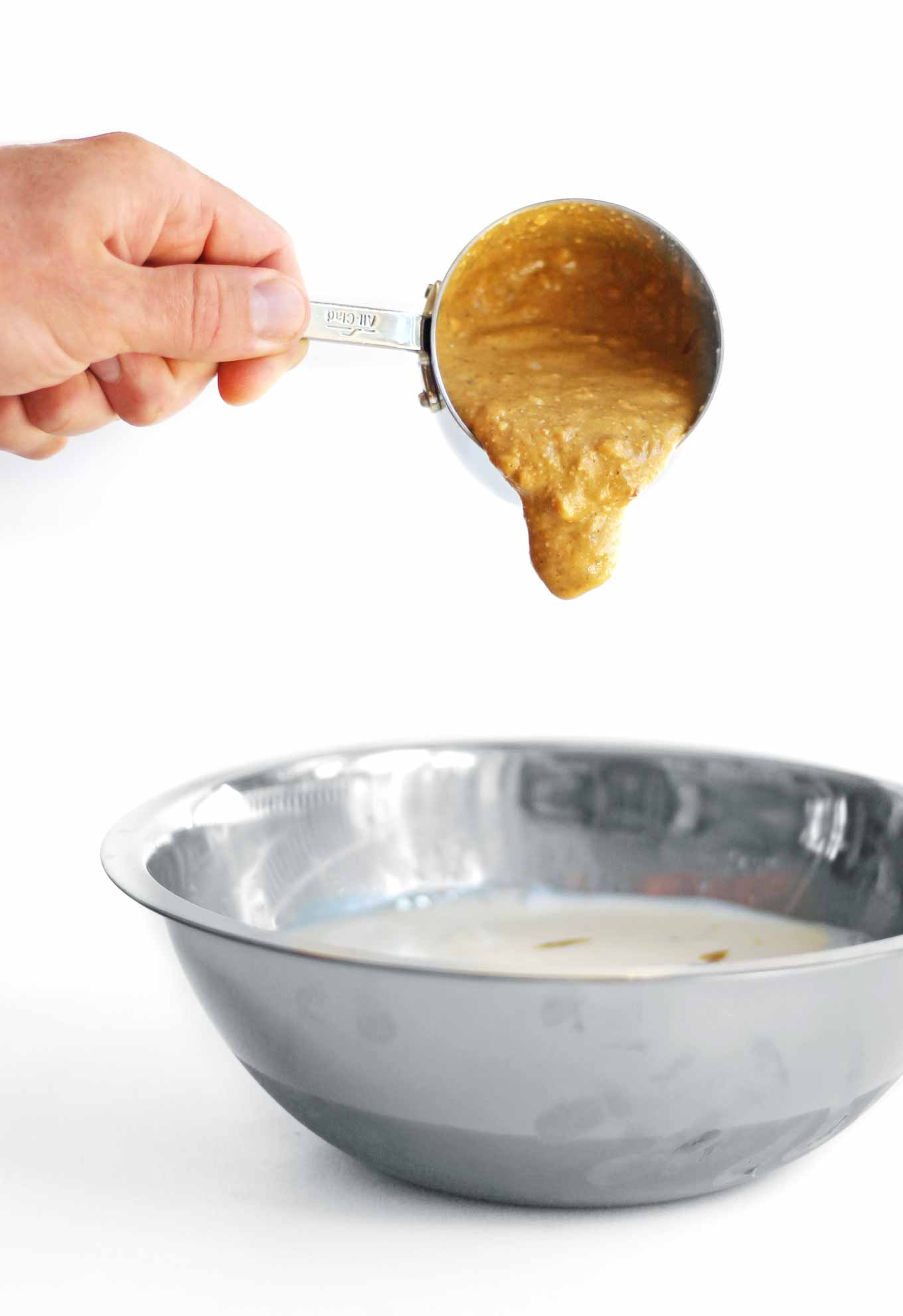 pouring peanut butter into a metal bowl