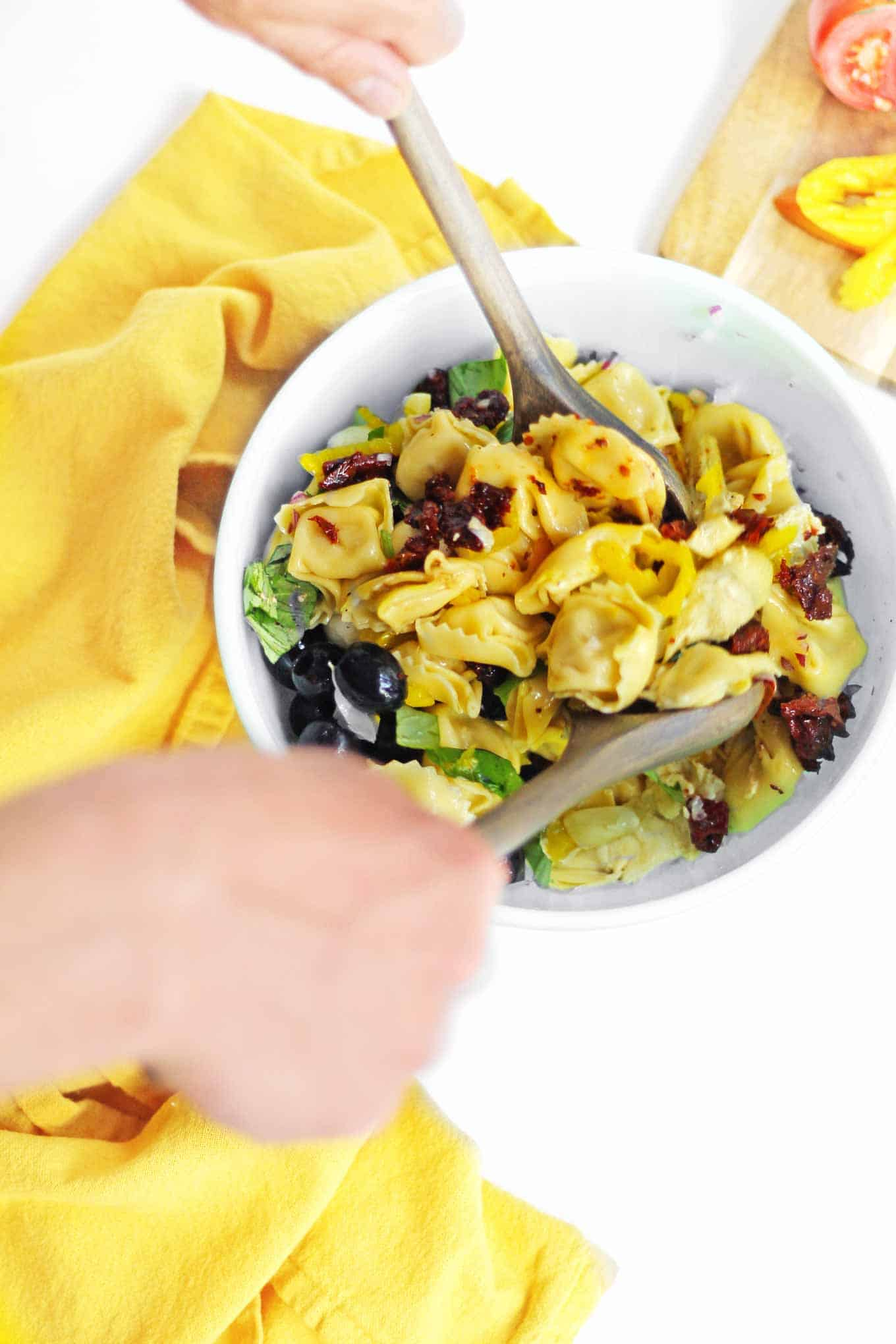 tossing a cheese tortellini pasta salad