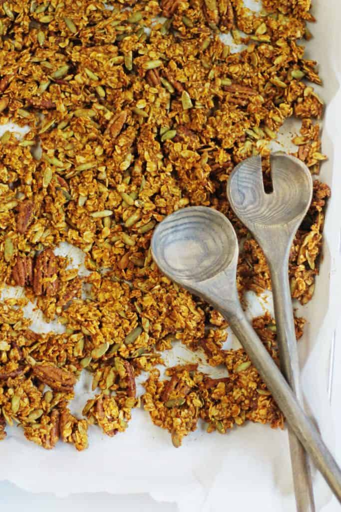 granola on a tray with wooden spoons