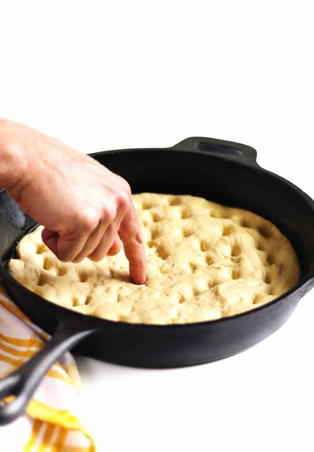 poking focaccia bread dimples