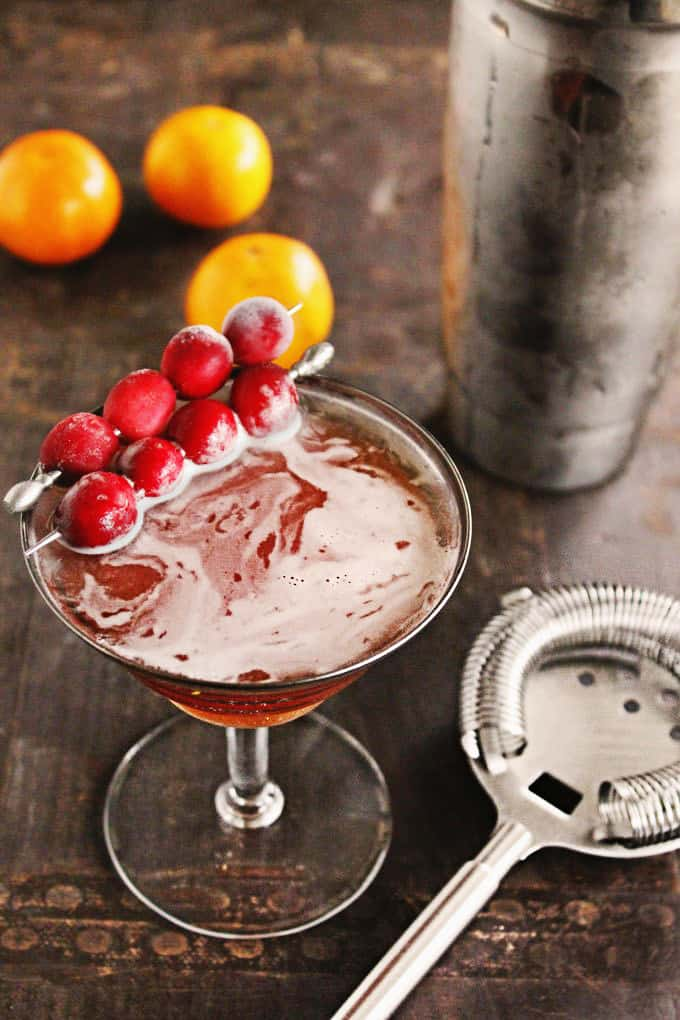 Holiday manhattan with cranberry garnish and oranges