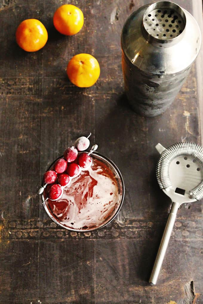 orange cranberry holiday manhattan flat lay with shaker and cocktail strainer