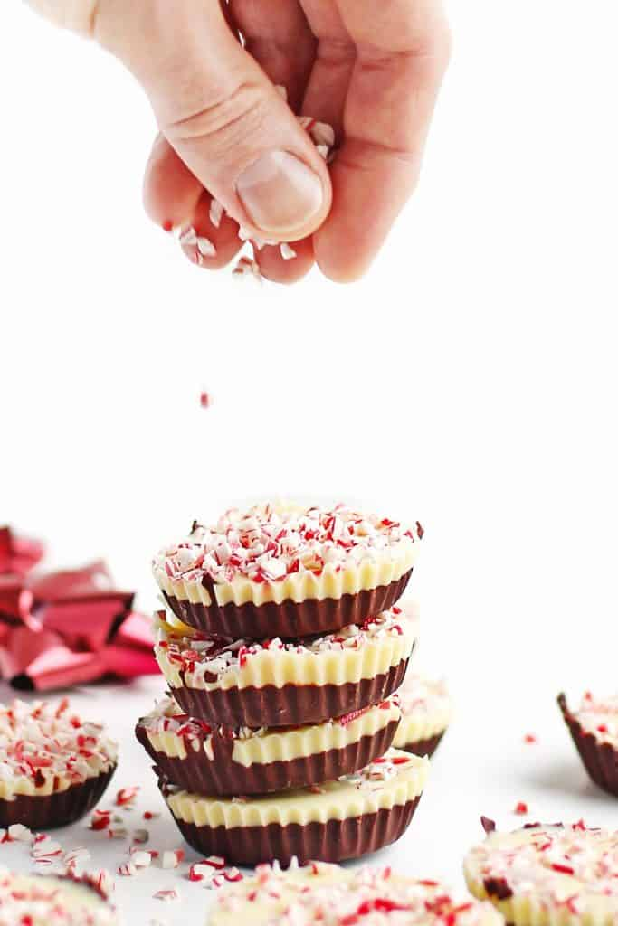 sprinkling candy cane on peppermint bark cups