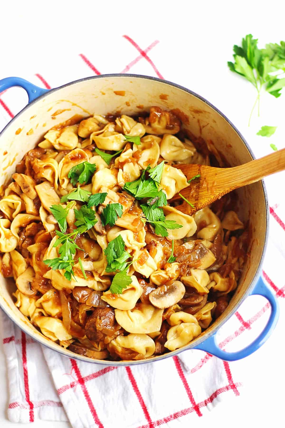 Cheese tortellini with caramelized onion sauce with a wooden spoon