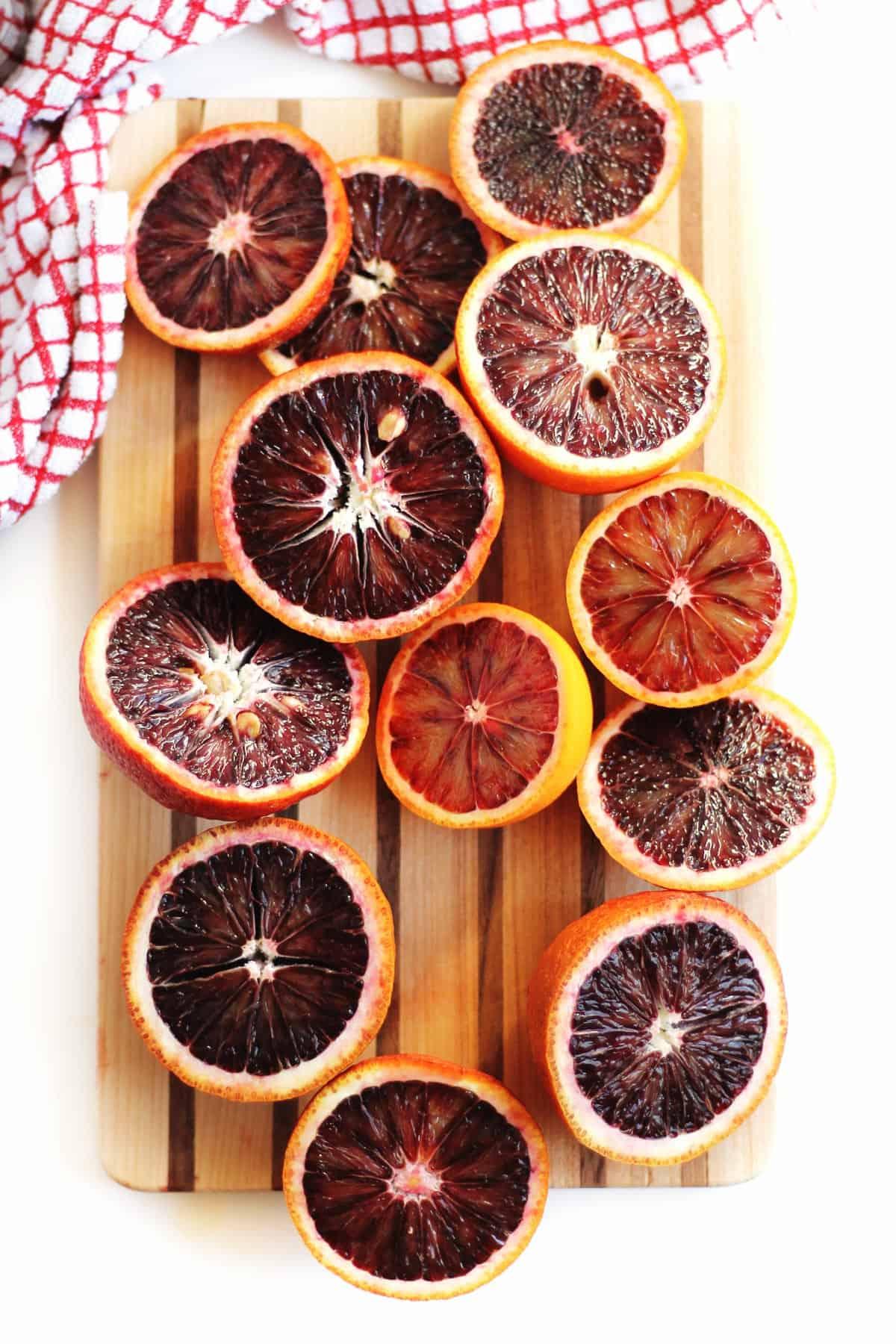 blood oranges sliced in half on a cutting board