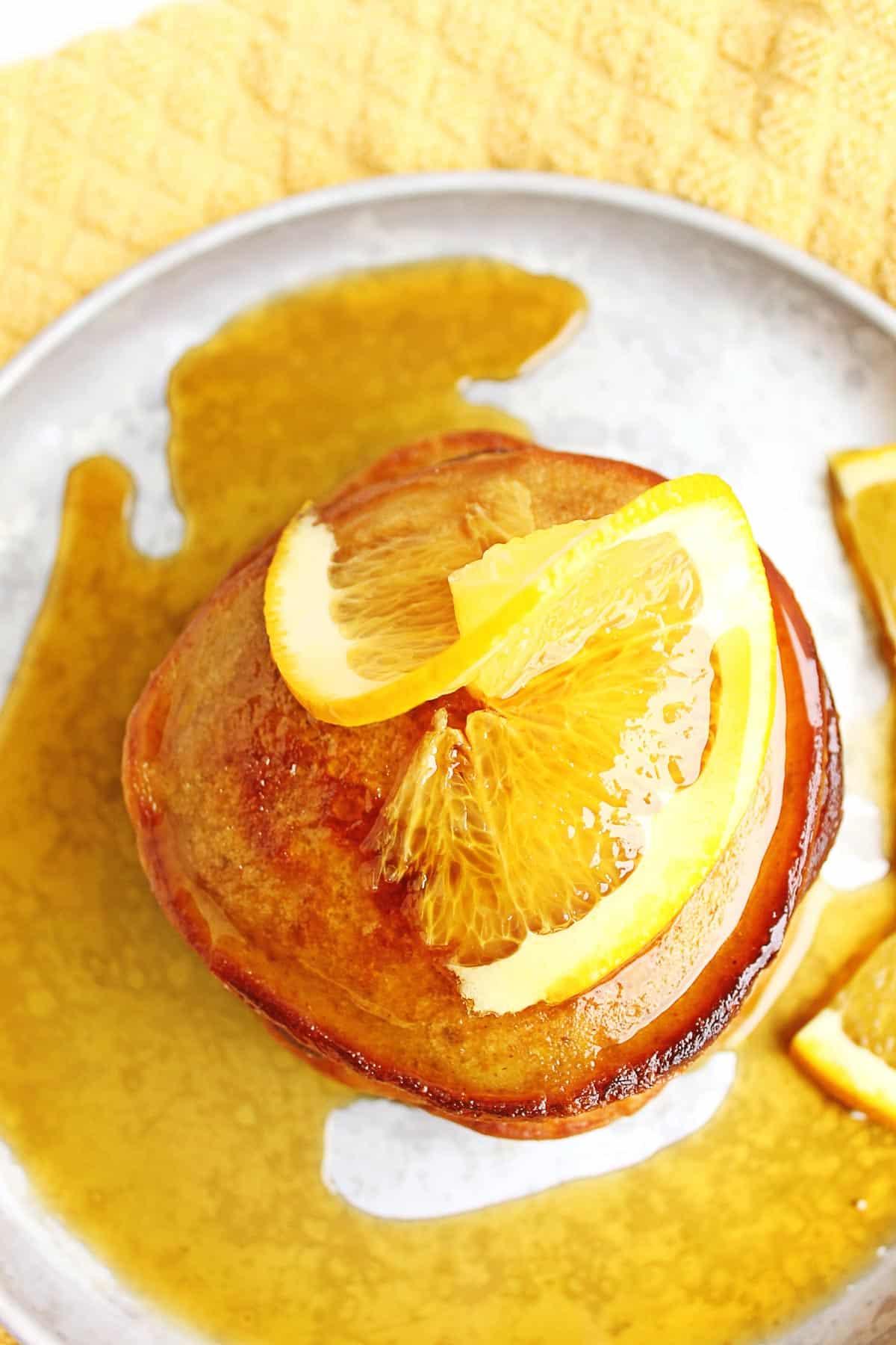 stack of orange pancakes with orange slice