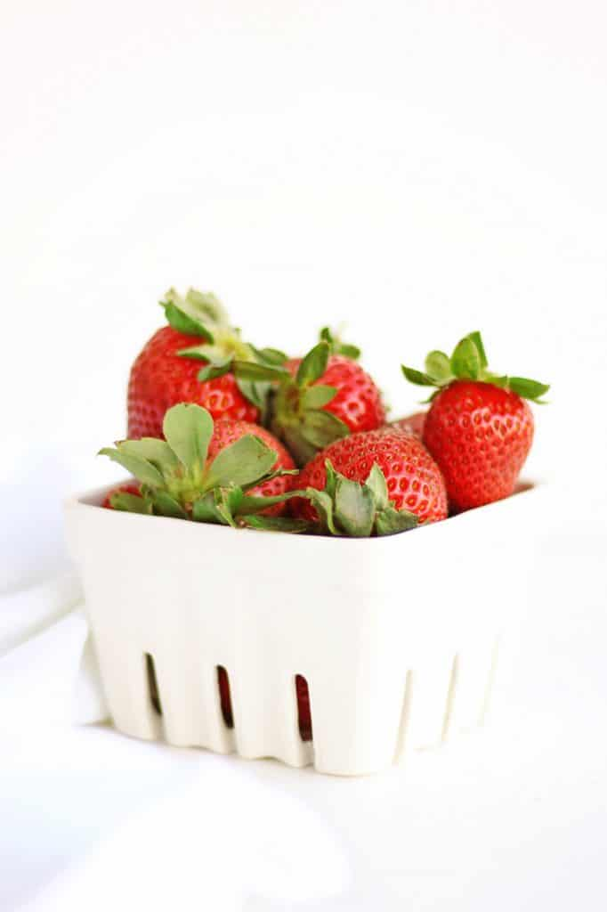 fresh strawberries in a white farmers market basket