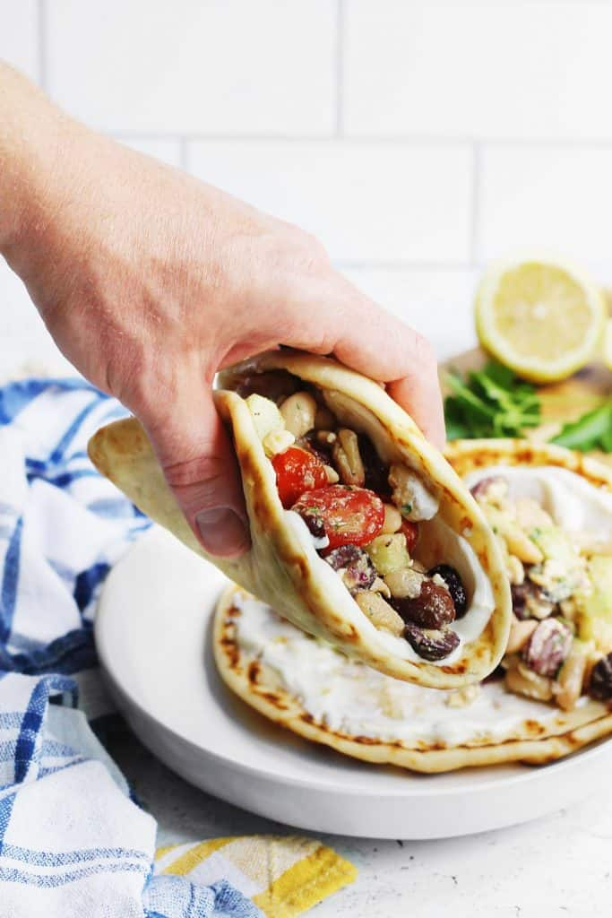 Vegetarian greek salad wraps picked up with a hand