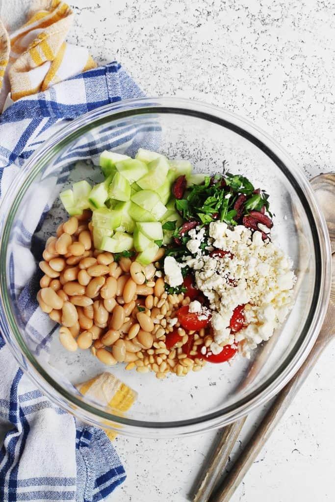 White bean greek salad ingredients in a glass bowl
