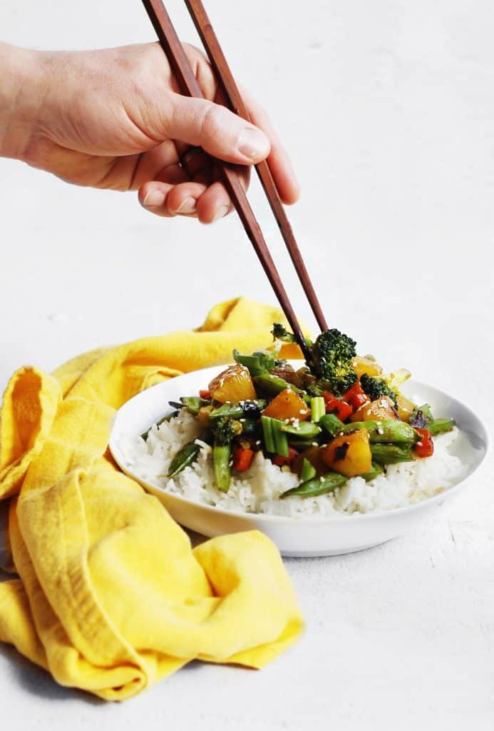 Teriyaki vegetable stir fry with rice pick up with chopsticks