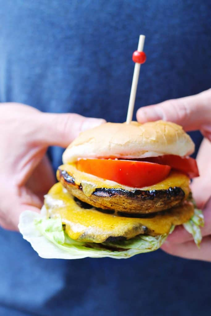 Man holding a portobello mushroom burger
