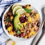 Black bean quinoa salad with avocado, cherries, and lime in a white bowl