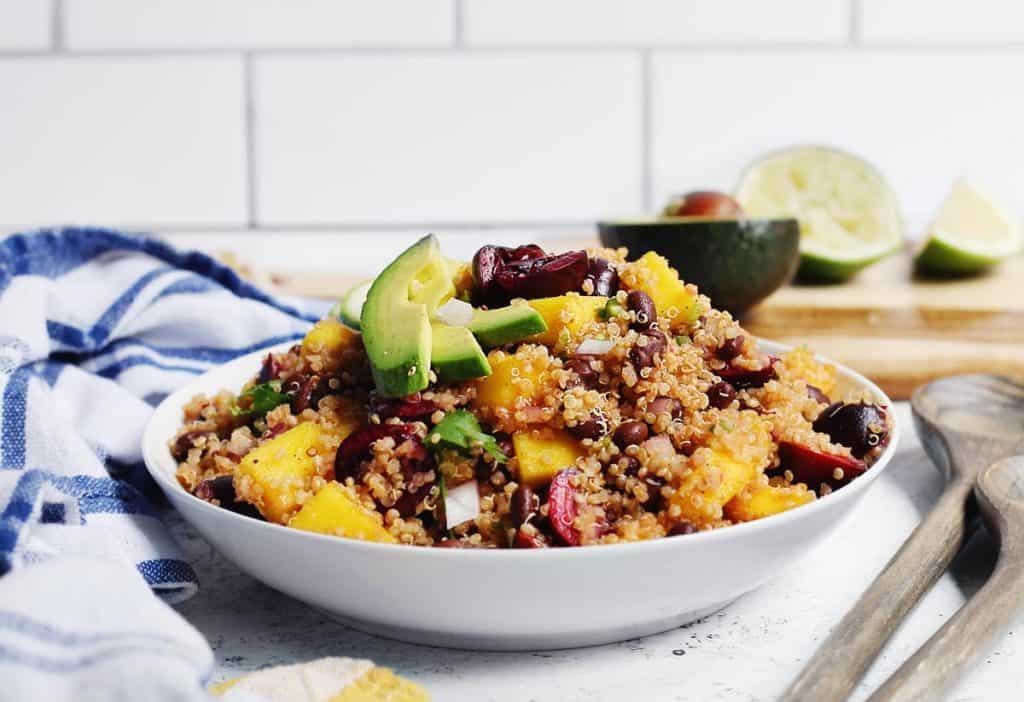 Quinoa salad with black beans, mango, and avocado in a white bowl