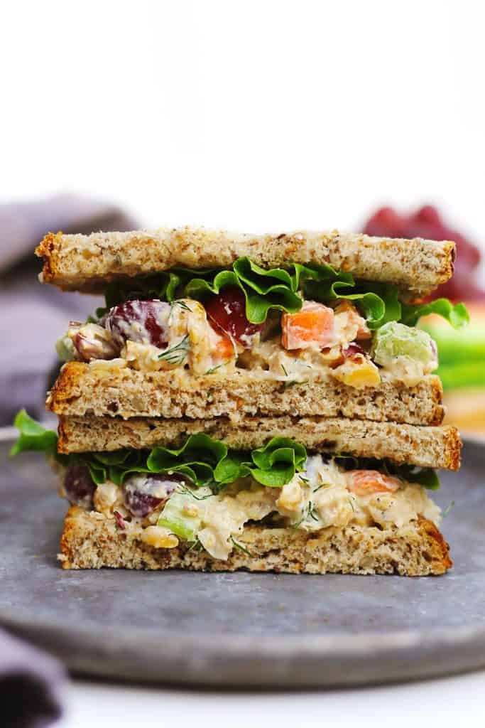 Vegetarian chickpea salad sandwich stack on a gray plate