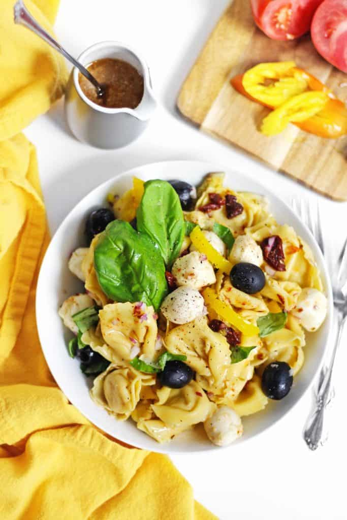 Italian tortellin pasta salad in a white bowl with a yellow napkin