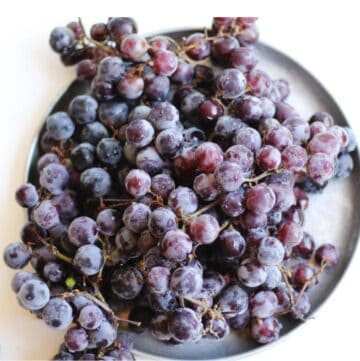 Concord grapes in a bunch on a silver plate