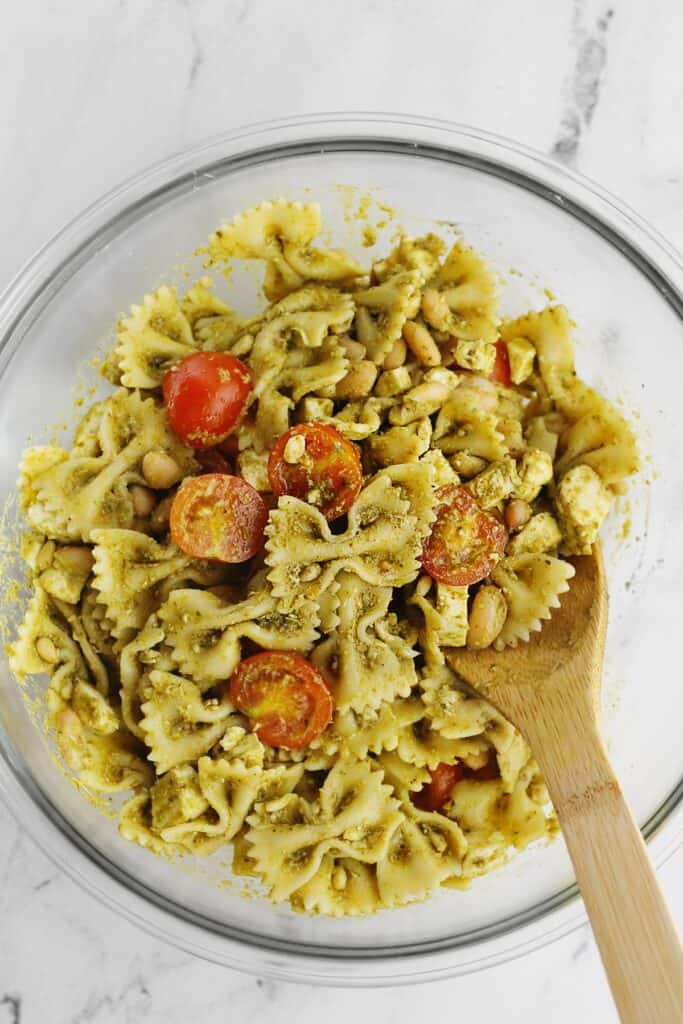 Pasta salad with pesto and tomatoes and a wooden spoon