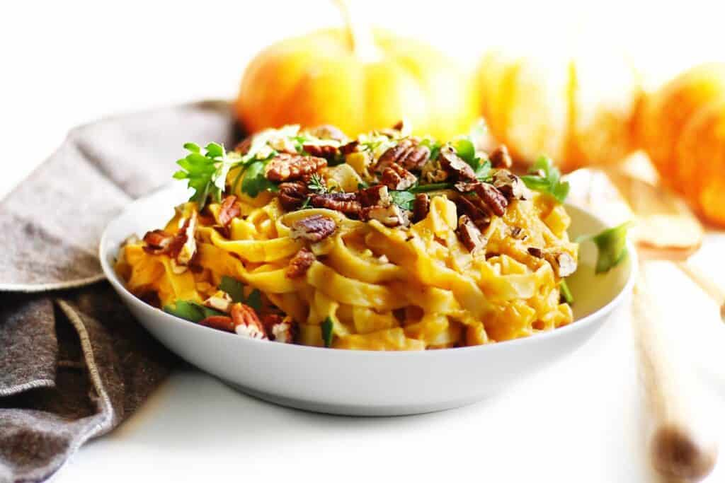 pumpkin pasta with pecans and parsley in a white bowl