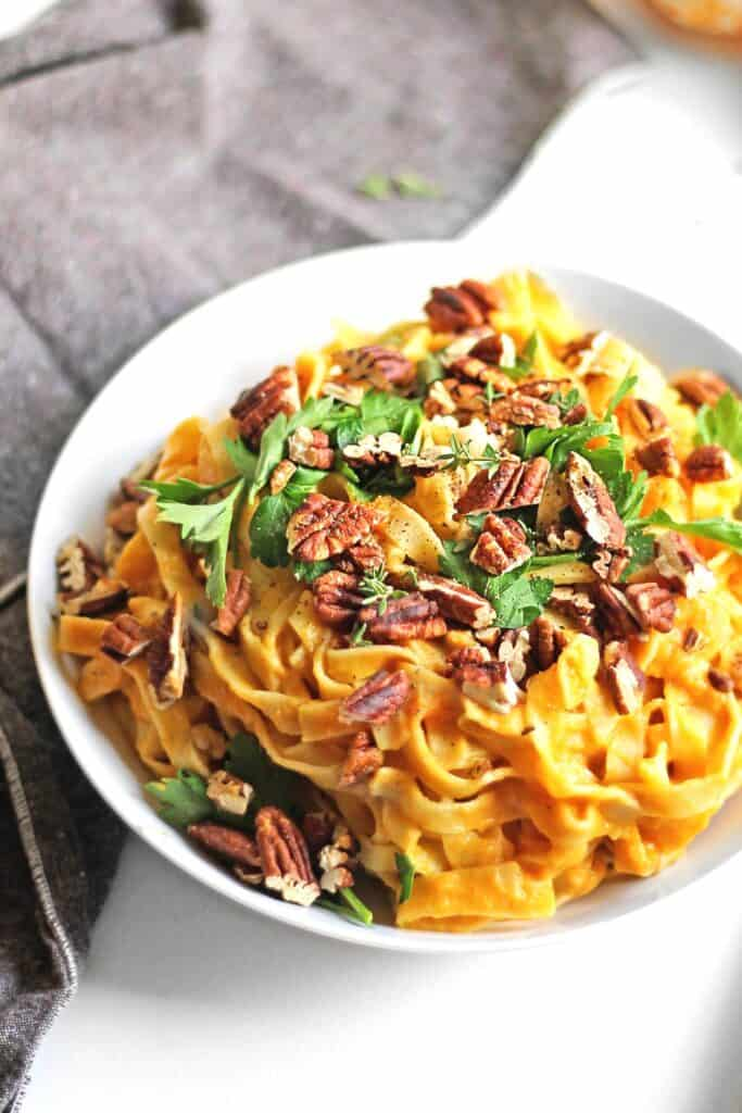 cauliflower pumpkin alfredo pasta with pecans and parsley in a white bowl