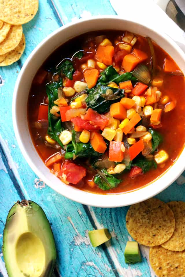 sopa azteca with red lentils and baby greens in a white bowl