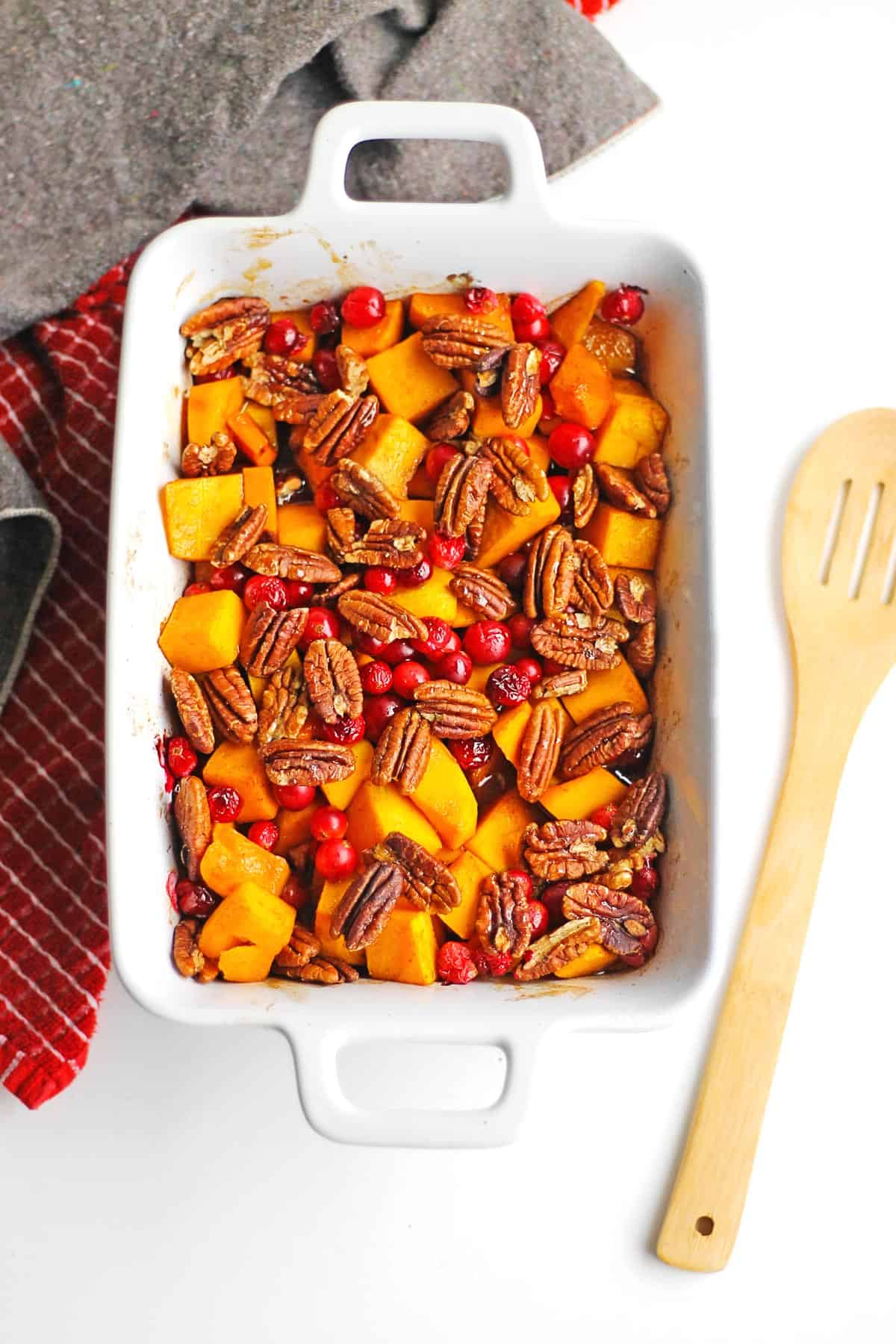 Roasted butternut squash with cranberries and pecans in a white pan