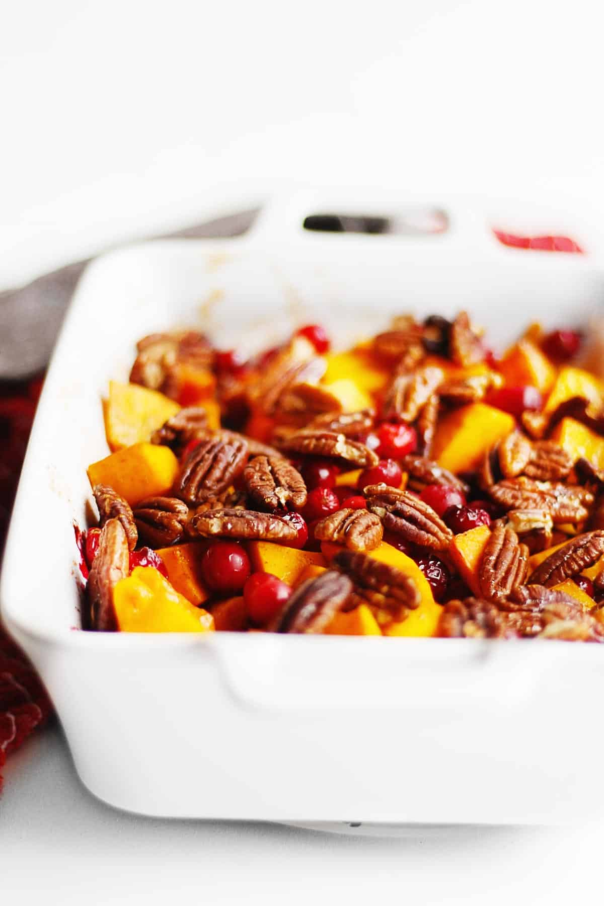 Cinnamon roasted butternut squash with cranberries and pecans in a white pan
