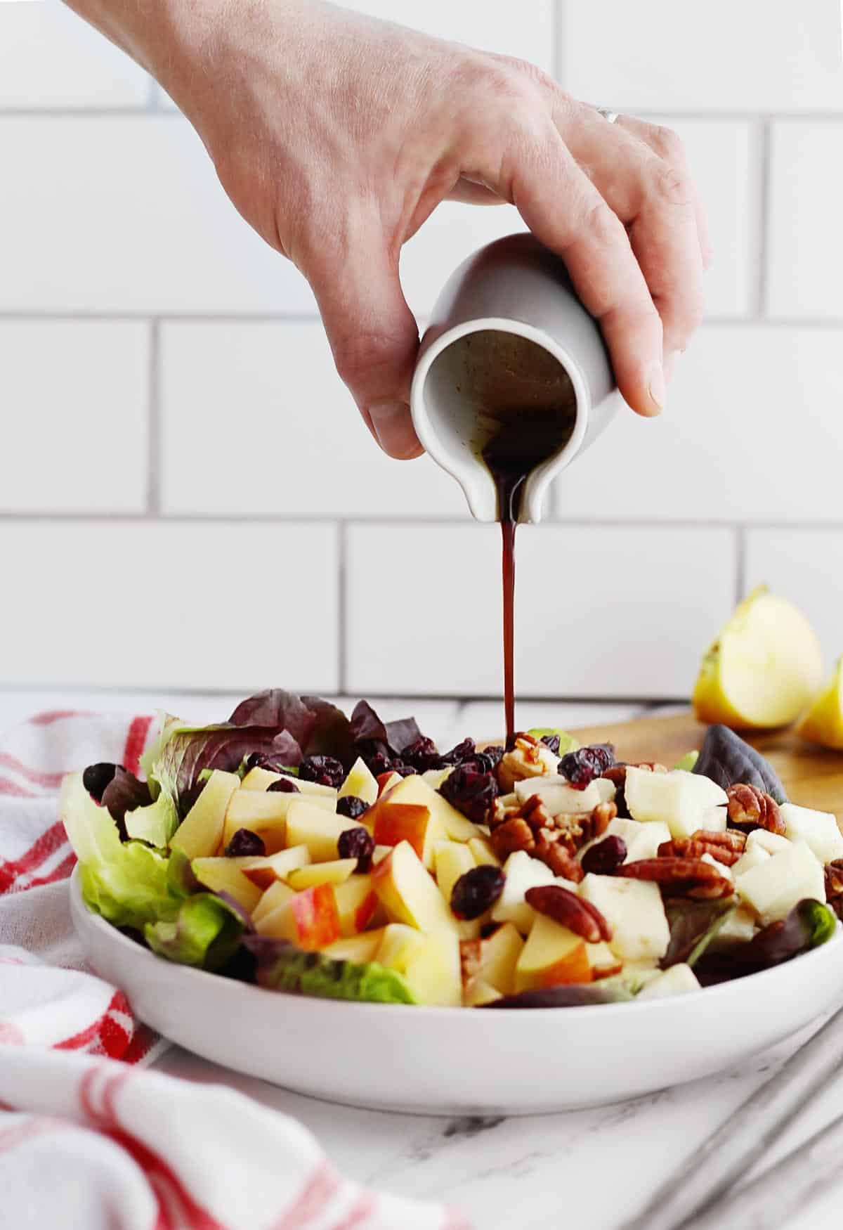 Fall salad with balsamic vinaigrette being poured on
