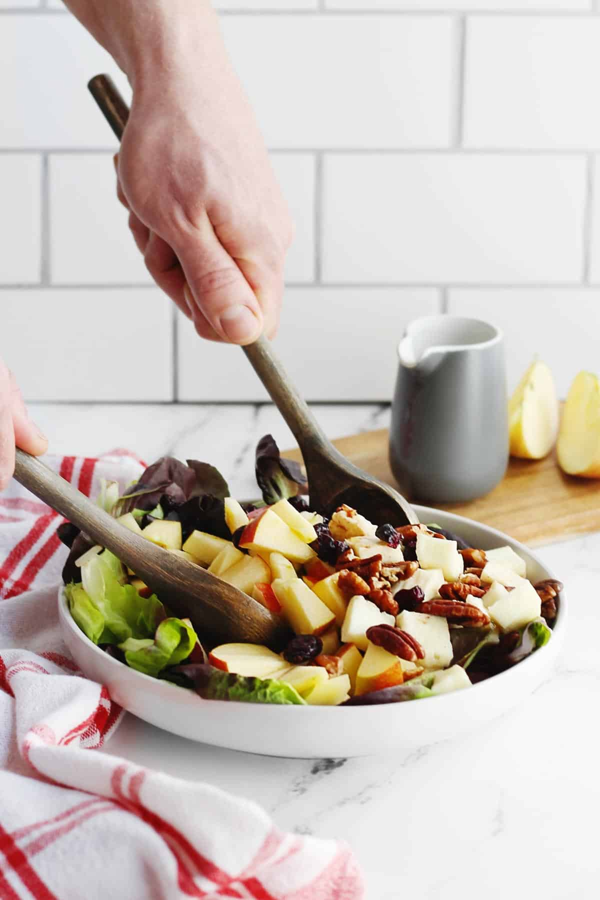 Warm apple halloumi salad being tossed