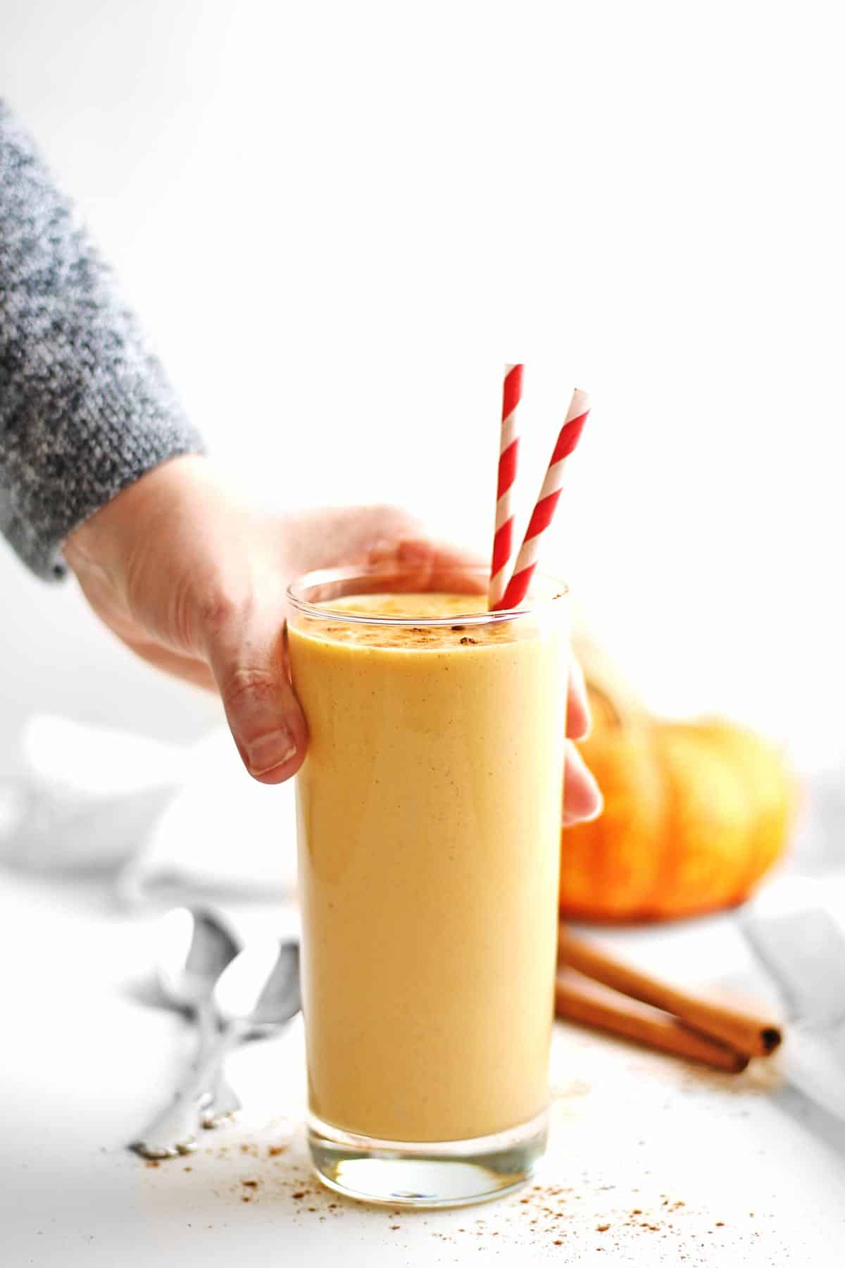 Pumpkin smoothie with hand picking it up