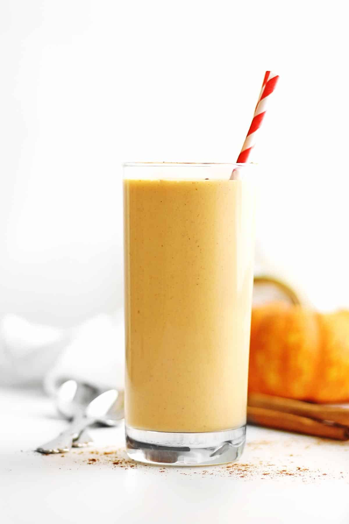Healthy pumpkin smoothie with red and white straw