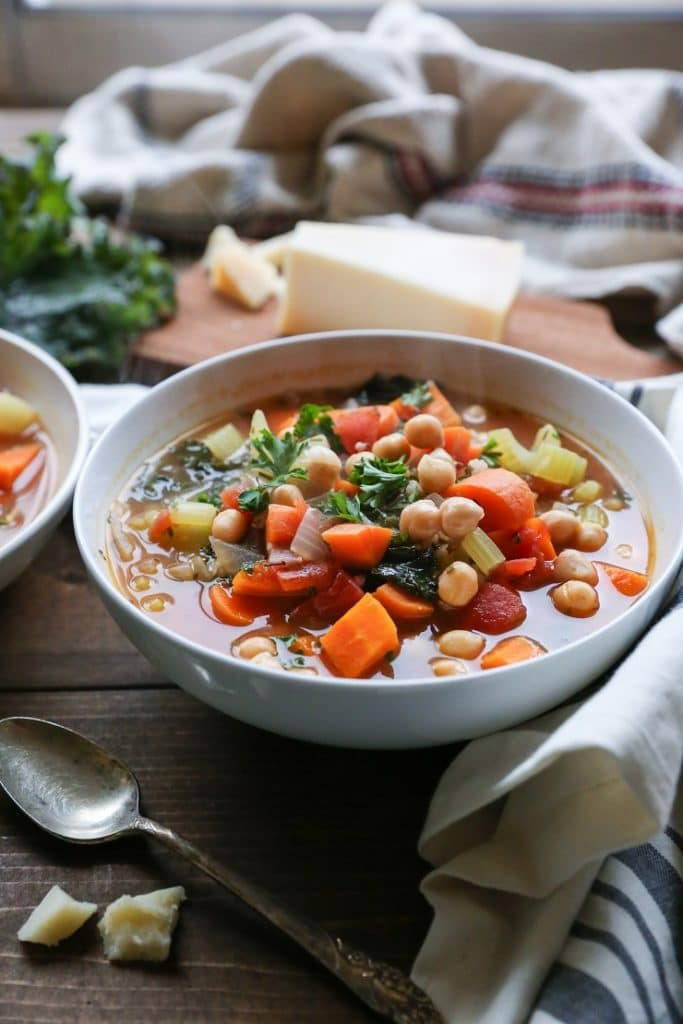 minestrone soup with rice and kale in a white bowl