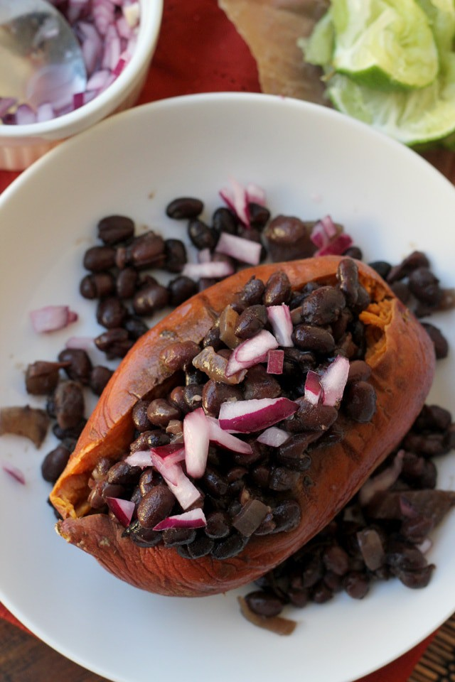 Slow cooker black bean ragout on roasted sweet potatoes with red onion