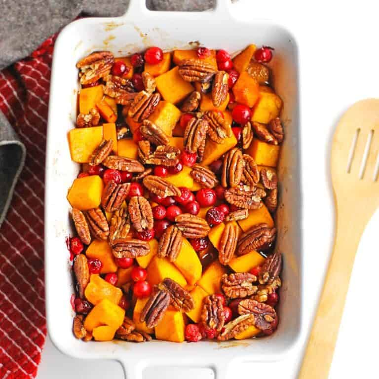 Butternut squash with cranberries and pecans in a white dish