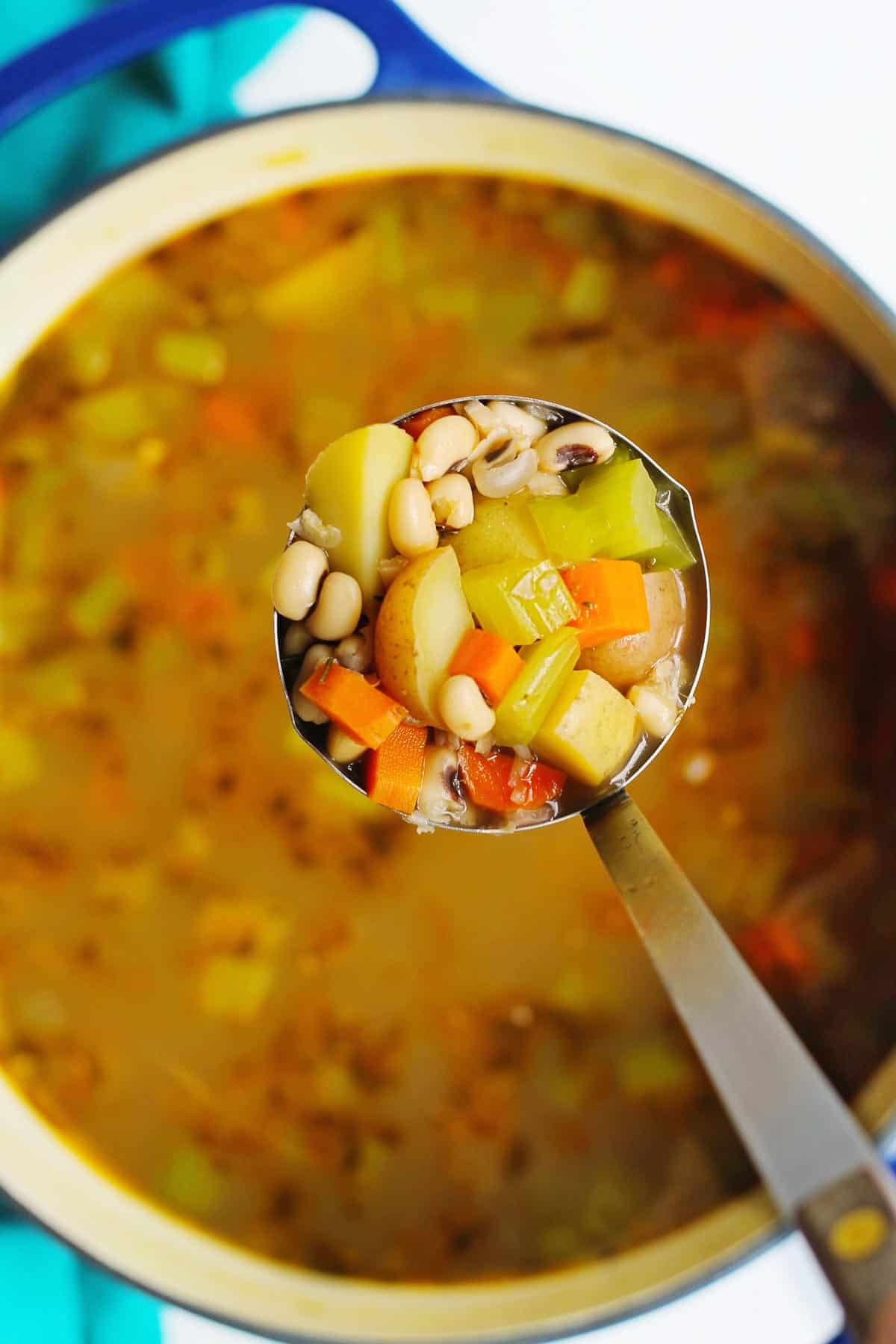 Black eyed pea vegetable soup in a ladle