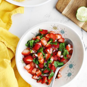 Fresh strawberry salsa in a white bowl with a silver spoon