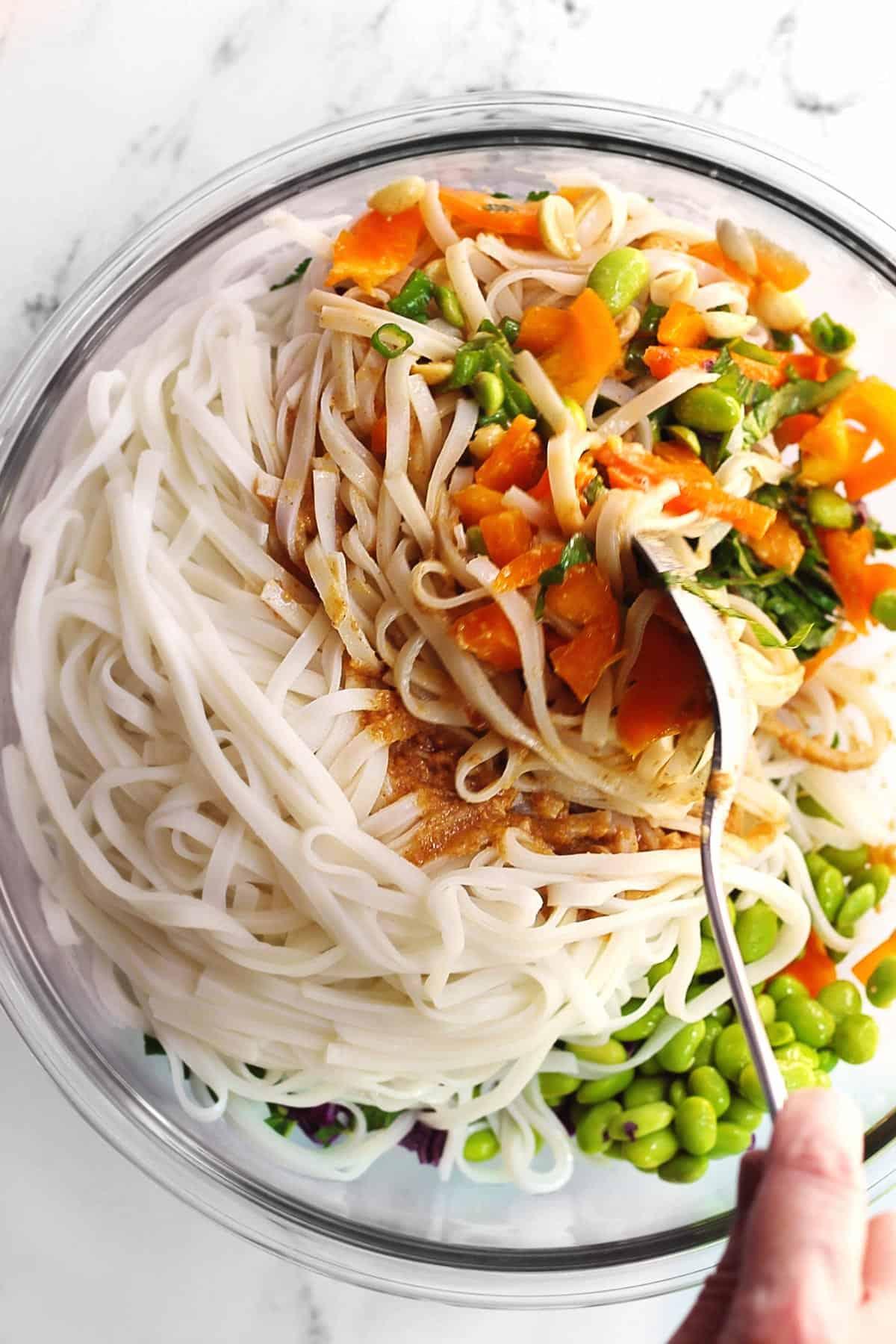 Vegan Thai peanut noodle salad being tossed together