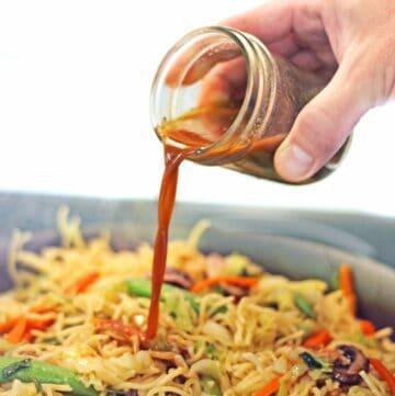 Vegan stir fry sauce pouring over noodles