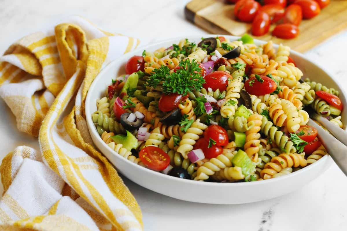 Italian pasta salad in a white bowl with a yellow and white napkin
