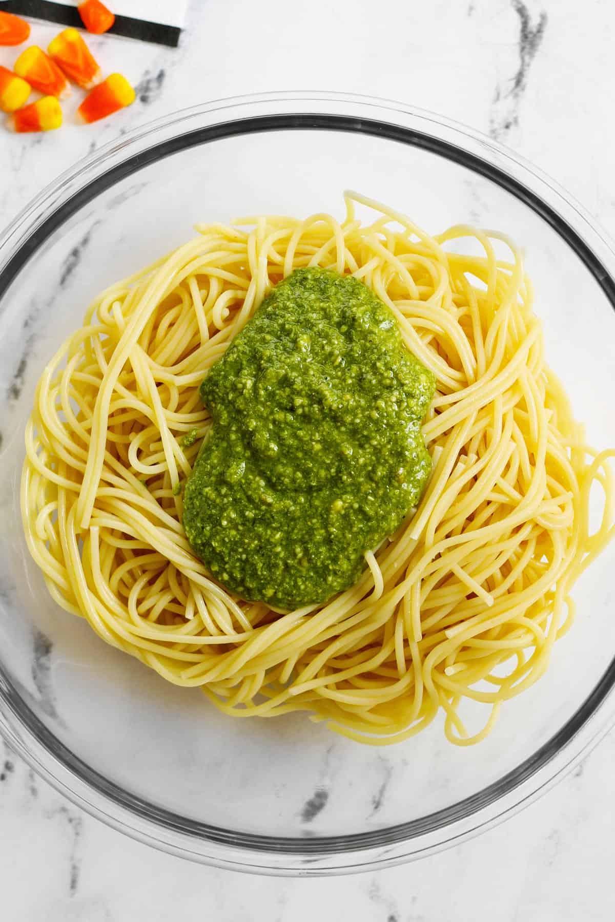 Pesto over spaghetti in a bowl